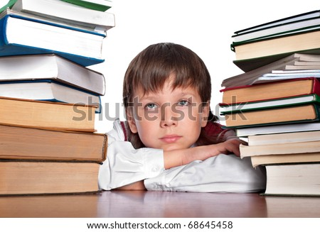 The schoolboy sits between two heaps of books and with melancholy thinks how to study all it - stock photo