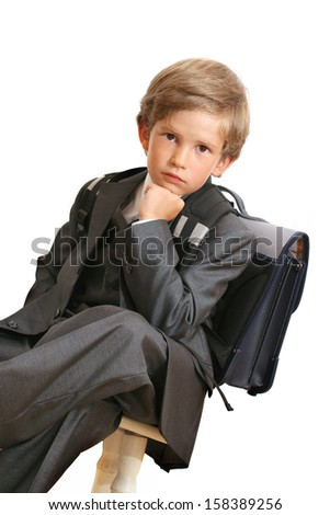 The schoolboy sits on a chair
