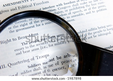 The second amendment to the constitution of the United States is shown under a magnifying glass. - stock photo