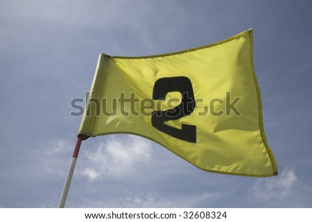 The second pin on a golf course green. Flag fluttering in the wind, against blue sky. Number two. - stock photo