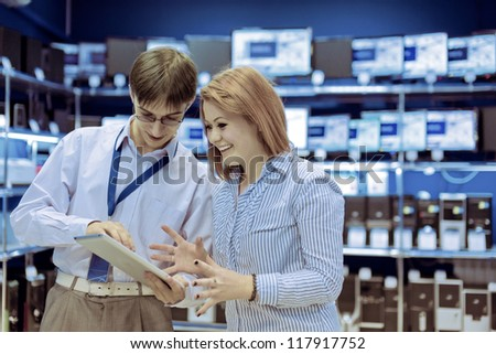 The seller-adviser shows the girl a new tablet computer - stock photo
