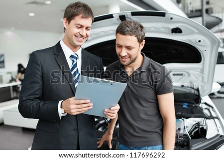 The seller and the buyer in the auto show - stock photo