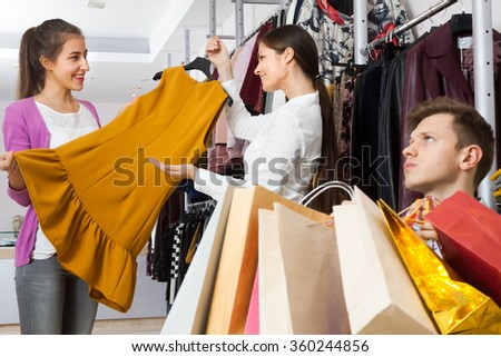 The seller in a clothing store offers young woman dress. A man waits sitting in a chair