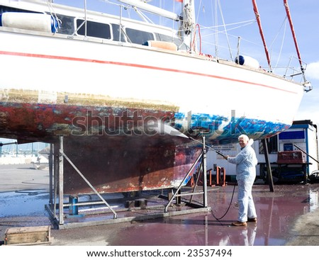 The senior man happy cleaning the bottom of a sailboat. - stock photo