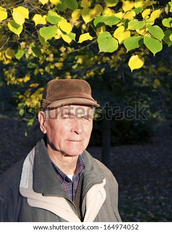 The senior man looking to the sun in sunny autumn day. Portrait. - stock photo