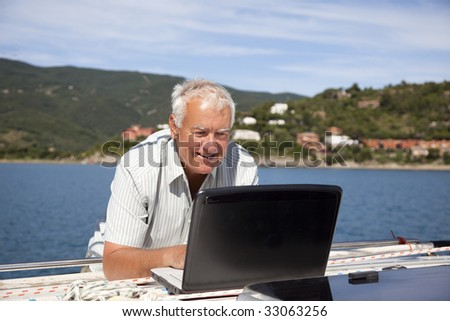 The senior man using the laptop on the sailboat. - stock photo