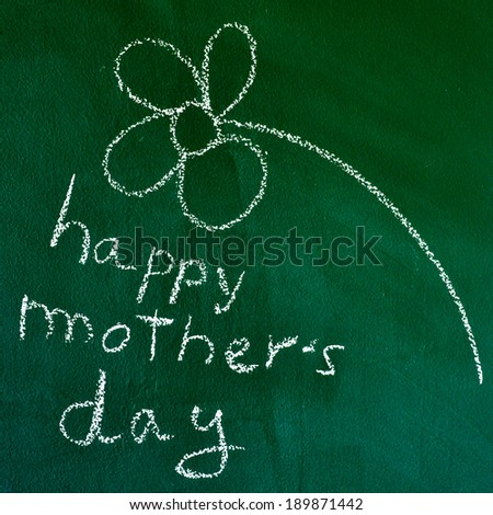 the sentence happy mothers day handwritten with chalk in a chalkboard, with a drawing of a flower - stock photo