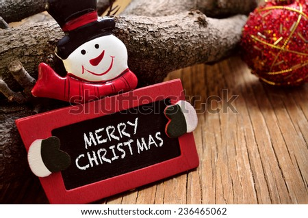 the sentence merry christmas written in a chalkboard in the the shape of a snowman on a rustic wooden surface - stock photo