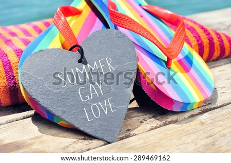 the sentence summer gay love written in a heart-shaped slate stone and a pair of rainbow flip-flops and a beach towel on a boardwalk above the ocean - stock photo