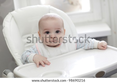 The serious baby sitting in highchair at home - stock photo