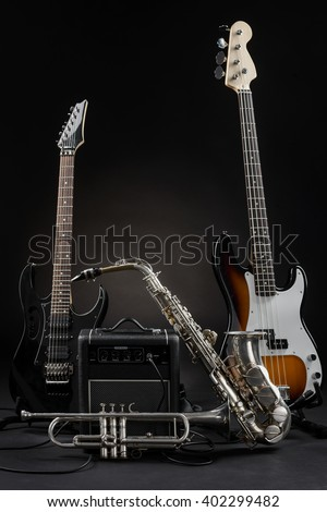 The set of musical instruments made of electric and bass guitar, amp, alt saxophone and trumpet. Nice music for soul. Composition of expensive professional equipment. - stock photo