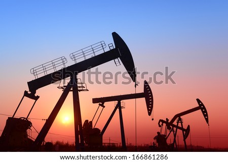 The setting sun is operation of the pumping unit   - stock photo
