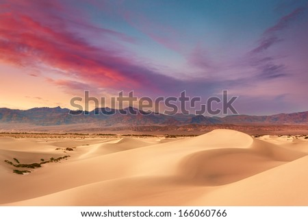 The setting sun sets the sky ablaze during a summer sunset on Mesquite Sand Dunes in Death Valley National Park.   - stock photo
