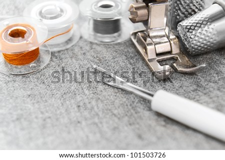 The sewing machine, threads and thimbles on a fabric. - stock photo