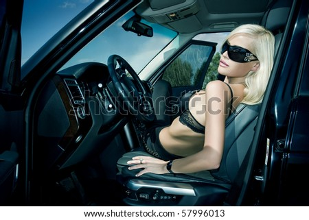 The sexual blonde in underwear in car salon - stock photo