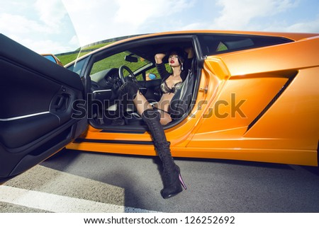 The sexual woman in lingerie in car salon - stock photo