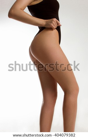 The sexy girl in a black bathing suit shows the slender body. Sport, diets, healthy lifestyle. Sexual legs. Beautiful buttocks. Sports body. - stock photo