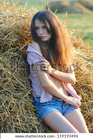 The sexy girl undresses near a haystack - stock photo