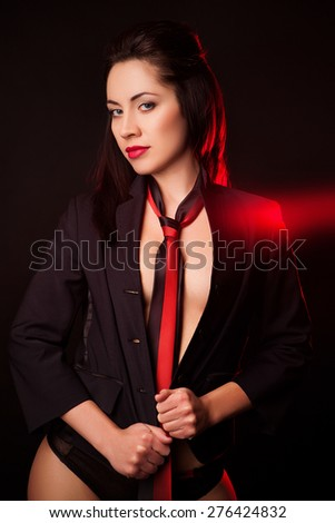 The sexy young woman in a black jacket and a red tie, on a black background with a red luminescence