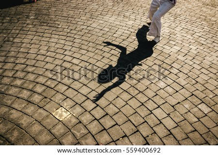 The shadow of a dancer projected in the floor.