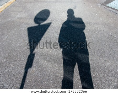 the shadow of a man on a sidewalk. anonymity of the big city. - stock photo
