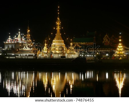 The Shan/Burmese style Wat Jong Klang temple reflected in the Nong Jong Kham pond in Mae Hong Son City, Northern Thailand.