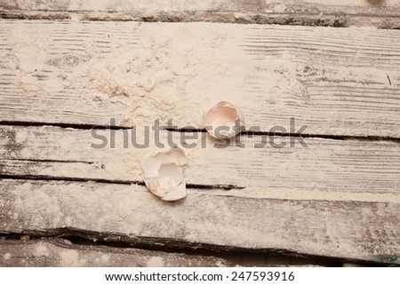 the shells of eggs on a wooden table with flour - stock photo