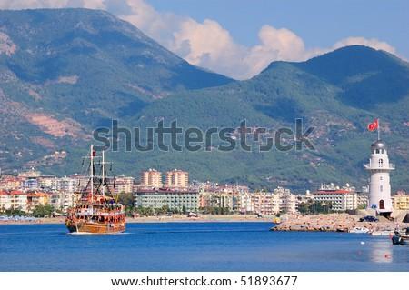 The ship floats near a beacon. Alanya. Turkey - stock photo