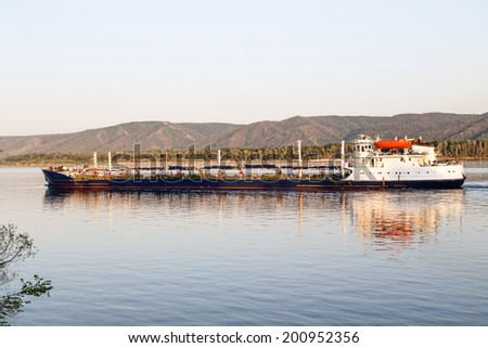 the ship tanker sailing on a river along the mountains. - stock photo