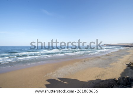 The shore of the Mediterranean Sea, with high beach rocks and waves hitting the brown sand beach, in Morocco in the sprin during a hot sunny day. - stock photo