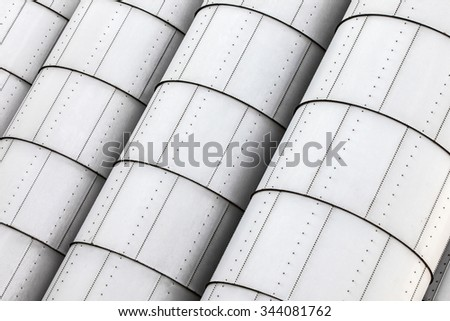The side of large industrial storage tanks comprised of sheet metal and nuts and bolts.
