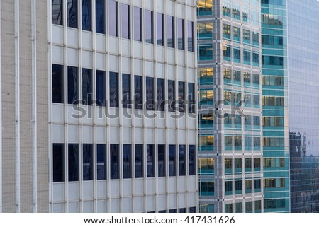 The side of three downtown office buildings at dusk. - stock photo