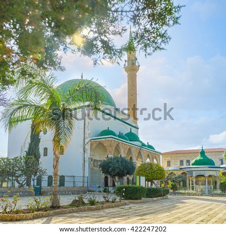 The side view of Al-Jazzar mosque and its small sabil among the green trees, Acre, Israel.