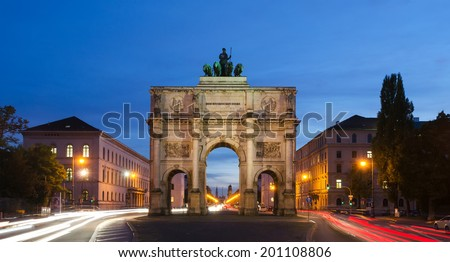 The Siegestor (english: Victory Arch) in Munich. This is a long exposure at dusk with traffic going around the arch - stock photo