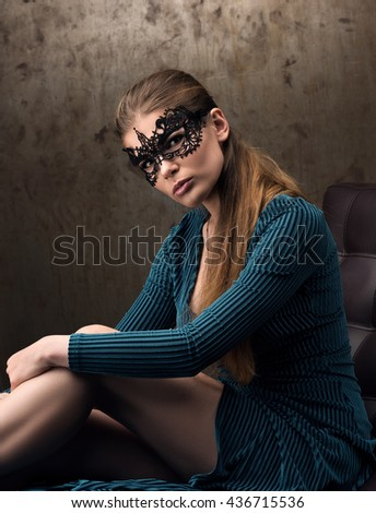 The sight of a beautiful young woman in black lace mask on the eyes. The model is sitting on the couch in a green dress. The metal wall in the background - stock photo