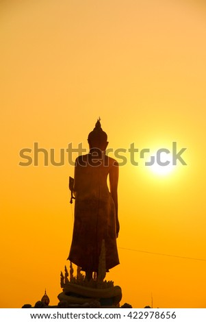 The silhouette Buddha's statue with yellow-orange background.