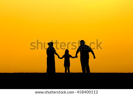 The silhouette of a happy family is father, mother and daughter walking in sunset.