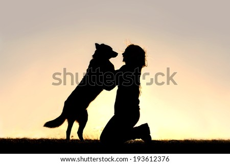 The silhouette of a happy German Shepherd mix dog is jumping up to greet a young woman, his master, isolated in front of a sunsetting sky.  Room for Copy-space. - stock photo