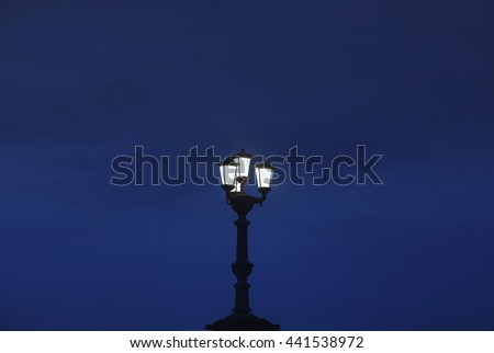 The silhouette of a lamppost in a street, over a deep blue sky, in the night.  - stock photo