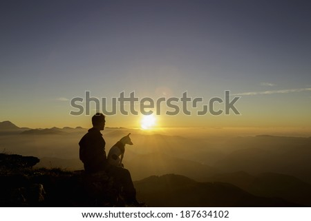The silhouette of a man and his dog sitting on the top of a mountain watching a sunset together. Italy. - stock photo