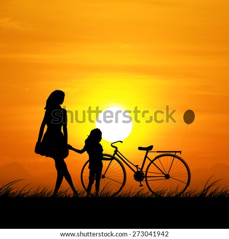 The silhouette of a mother and daughter during sunset. - stock photo