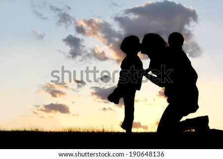 the Silhouette of a mother and her two young children; a little boy and his baby brother are playing outside at sunset, hugging and kissing. - stock photo