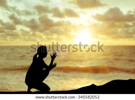 The silhouette of a person praying to God at sunset.