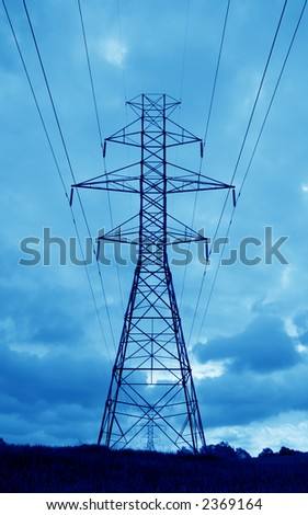 The silhouette of a power lines and towers against blue sky. - stock photo