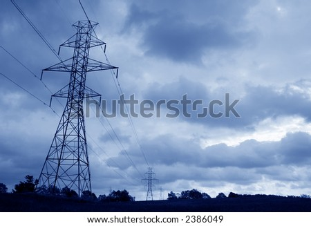 The silhouette of a power lines and towers against blue sky.