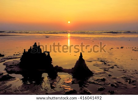The silhouette of a sand castle on the sand during sunset, Sand castle near the sea, Beach background, Sand castle on the beach, Peaceful landscape, Ruined sandcastle on the beach at sunset,  - stock photo