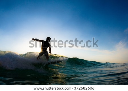 The silhouette of a surfer riding a wave.  - stock photo