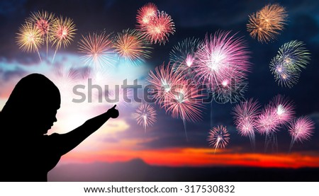 The silhouette of a young girl watching a fireworks display during sunset. Beautiful firework display for celebration. Sunset background. Sunset with firework background. Hand pointed fireworks.