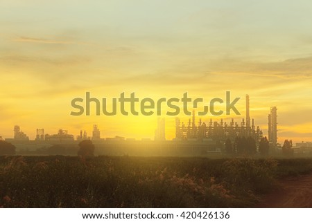 The Silhouette of chemical plant  with meadow at sunrise (select focus) - stock photo