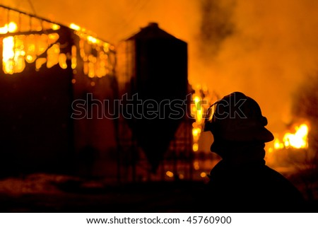 The silhouette of Fire Fighter watching a barn burn - stock photo